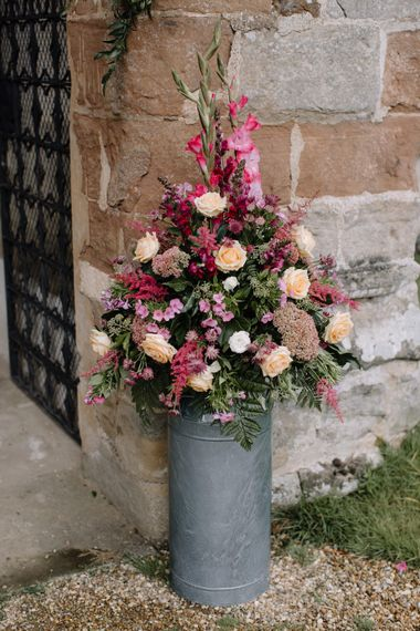 Deep Pink Milk Churn Wedding Flowers | Rural Wedding in a Sailcloth Tent on Stanford Hall Estate, Northamptonshire | Rebecca Goddard Photography