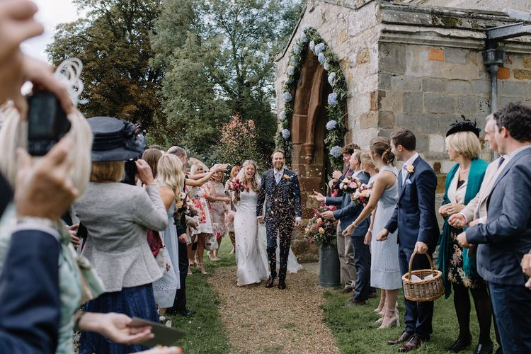 Confetti Exit | Bride in a Temperley Cressida Gown | Groom in Sandro Suit | Rural Wedding in a Sailcloth Tent on Stanford Hall Estate, Northamptonshire | Rebecca Goddard Photography