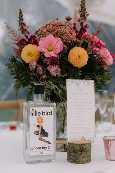 Rustic Centrepieces with Coral Flowers & Gin Bottles | Rural Wedding in a Sailcloth Tent on Stanford Hall Estate, Northamptonshire | Rebecca Goddard Photography