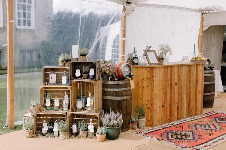 Rustic Wooden Crate & Gin Bottle Table Plan & Bar | Rural Wedding in a Sailcloth Tent on Stanford Hall Estate, Northamptonshire | Rebecca Goddard Photography