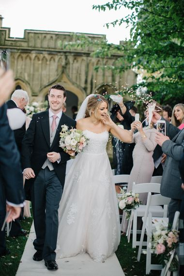 Confetti Exit | Wedding Ceremony | Bridein Princess Gown | Groom in Top Hat & Tails | Outdoor Pastel Country Garden Wedding at Barnsley House in Cirencester | M and J Photography | Motion Farm Wedding Films