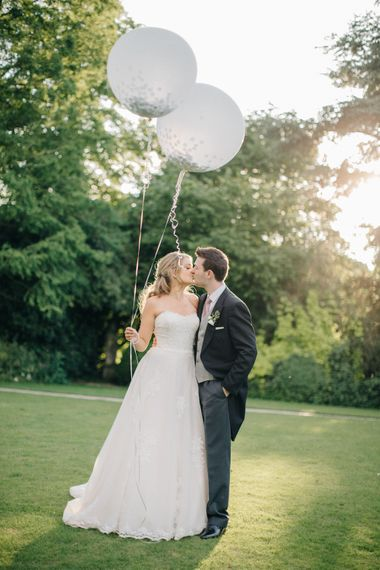 Giant Balloons | Bride in Lace Princess Gown | Groom in Traditional Morning Suit | Outdoor Pastel Country Garden Wedding at Barnsley House in Cirencester | M and J Photography | Motion Farm Wedding Films