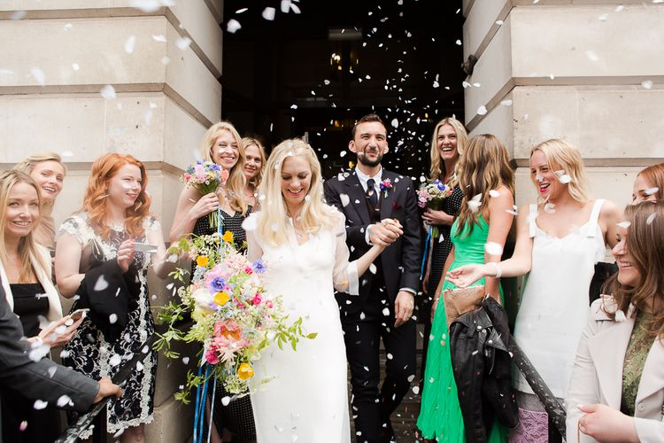 Confetti Moment at Camden Town Hall Wedding Ceremony with Bride in Charlie Brear Wedding Dress, Bright Bouquet & Groom in Paul Smith Suit