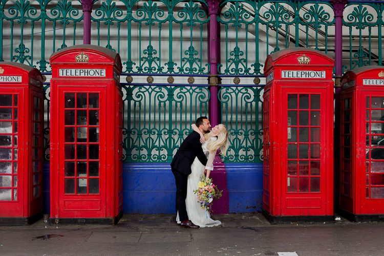 Bride in Charlie Brear Wedding Dress & Groom in Paul Smith Suit next to Red Telephone Boxes