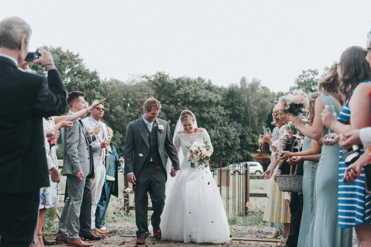 Confetti Moment with Bride in Pronovias White One Wedding Dress & Groom in Grey Morning Suit