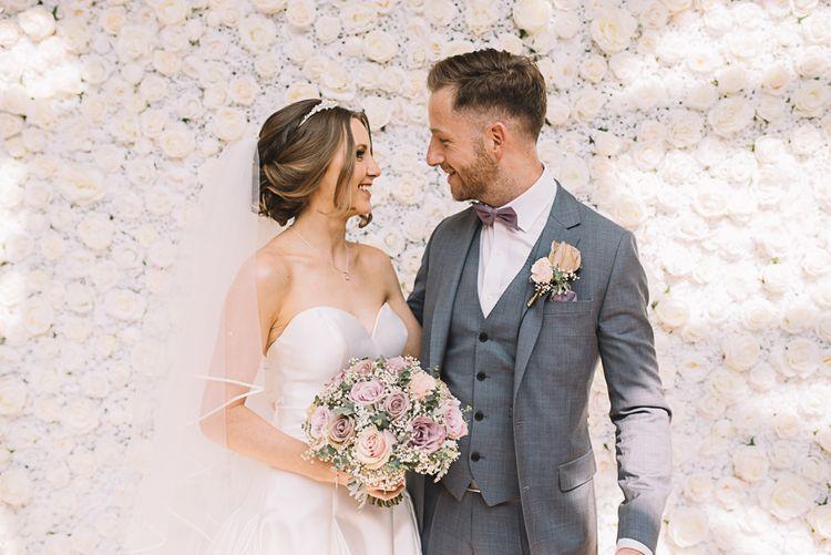 Flower Wall | Bride in Ronald Joyce Wedding Dress | Groom in Grey Moss Bros Suit | The Orangery Maidstone | Lucie Watson Photography | TDH Media Films