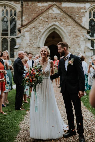 Confetti Exit | Bride in Lace & Tulle Gown | Groom in Black Suit & Liberty Print Bow Tie | Colourful DIY Barn Wedding at The Manor Barn, Cambridge | Meghan Lorna Photography