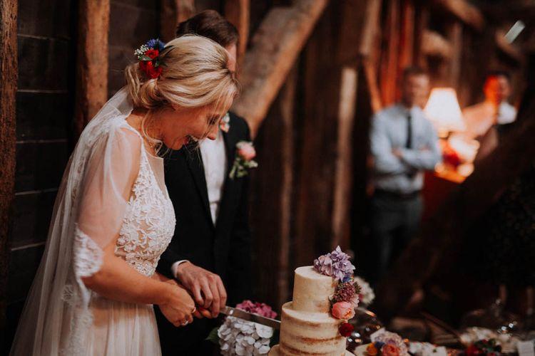 Bride & Groom Cutting the Cake | Colourful DIY Barn Wedding at The Manor Barn, Cambridge | Meghan Lorna Photography