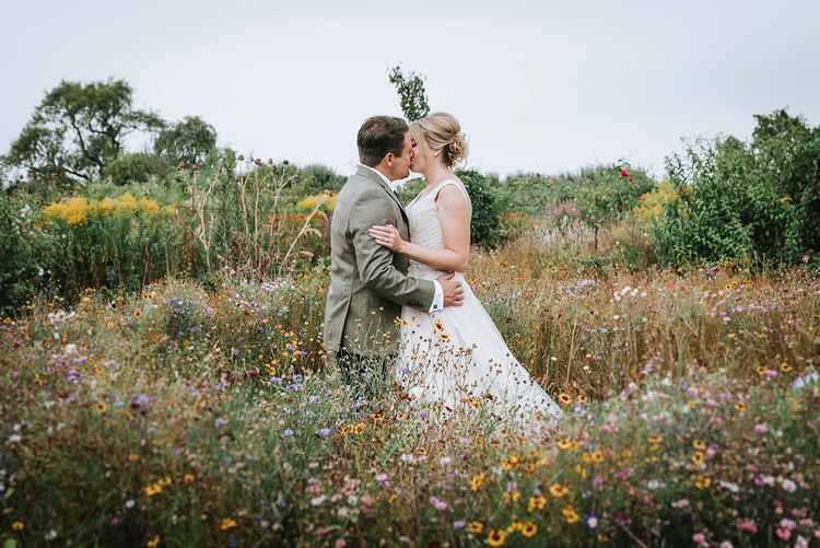 Bride in Phil Collins Bridal Gown & Groom in Chino's & Tweed Jacket at Helmingham Hall Gardens