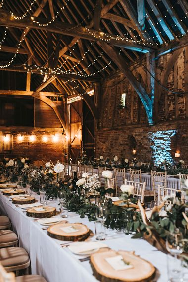 Rustic Barn Reception with Wood Slices, Antlers, Fairy Lights & Greenery