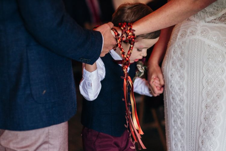 Wedding Ceremony Hand Fastening | Bride in Lenora Watters Wtoo Lace Bridal Gown | Groom in Ted Baker Chinos & Reiss Waistcoat & Blazer | Bohemian Tipi Wedding Weekend at Fforest, Wales | Naomi Jane Photography