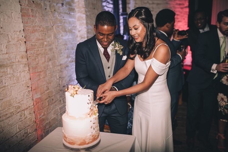 Cutting the Cake | Bride in Reformation Poppy Gown | Groom in Tailored The Bespoke Club Navy Suit | Stylish London Wedding Planned by Revelry Events | Story + Colour Photography