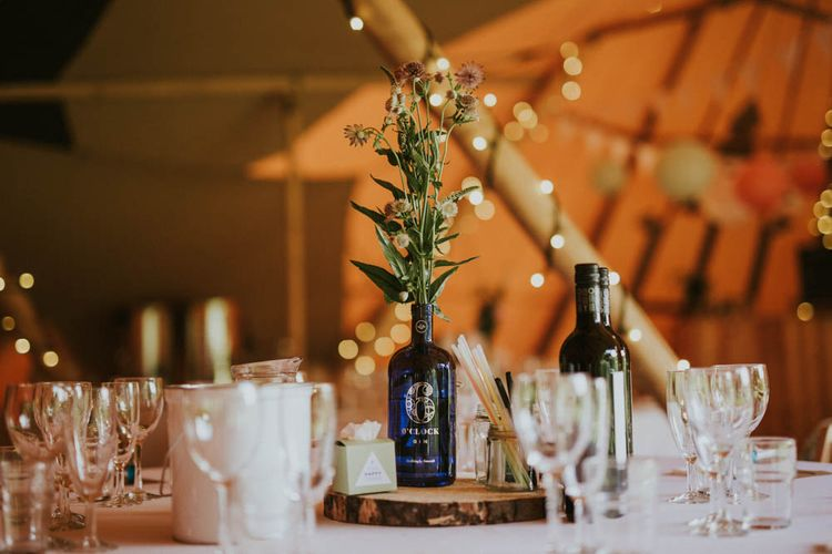 Tree Slice & Bottle Centrepiece | Rustic Tipi Wedding at The Grange, Belluton, Pensford | Images by Felix Russell-Saw & Ryan Winterbotham