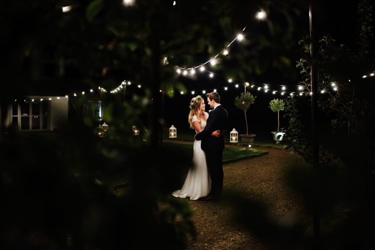 Festoon Lights | Bride in Bespoke Suzanne Neville Scarlett Bridal Gown | Groom in Herbie Frogg Suit & Liberty Print Mrs Bow Tie | The Lou's Photography