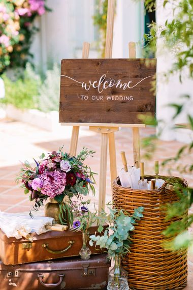 Wooden Wedding Welcome Sign with Vintage Suitcases & Parasols | Jewel Coloured Spanish Wedding Planned & Styled by Rachel Rose Weddings | Anna Gazda Photography