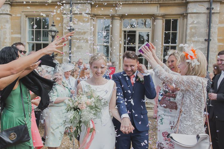 Confetti Moment | Bride in Justin Alexander Gown | Groom in Moss Bros Suit | Outdoor Peach Wedding at Courteenhall House in Northamptonshire Planned by Your Story Events | Ferri Photography