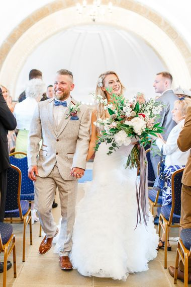 Wedding Ceremony at Normanton Church on Rutland Water | Pronovias Wedding Dress | Groom in Cream Herringbone Tweed Suit from Marc Darcy | White Stag Wedding Photography