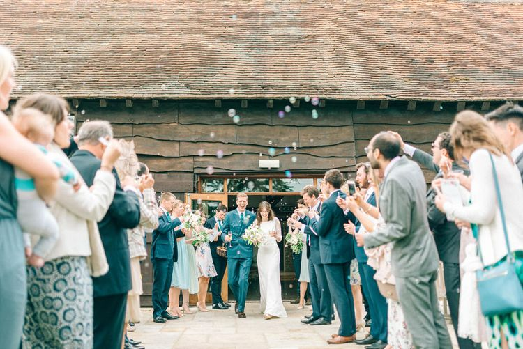 Confetti Exit   Bride in Fred & Ginger Bridal Design Gown   Groom in Navy Mullen Mullen Suit   Pastel Spring Wedding at Loseley Park Barn   Sarah-Jane Ethan Photography   Captured Media Weddings Film