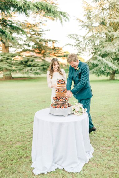 Cutting The Cake   Bride in Fred & Ginger Bridal Design Gown   Groom in Navy Mullen & Mullen Suit   Pastel Spring Wedding at Loseley Park Barn   Sarah-Jane Ethan Photography   Captured Media Weddings Film