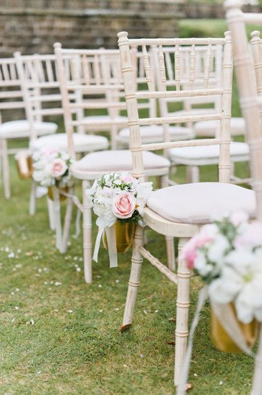 Outdoor Ceremony Aisle Chair Flower Decor   Wedding at Pennyhill Park, Surrey Planned by Something Blue Weddings   Anushe Low Photography   Reel Weddings Film