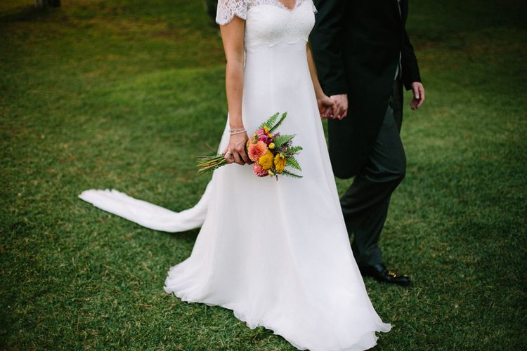 Bride in Xavier González Wedding Dress & Bright Bouquet with Groom in Traditional Morning Suit