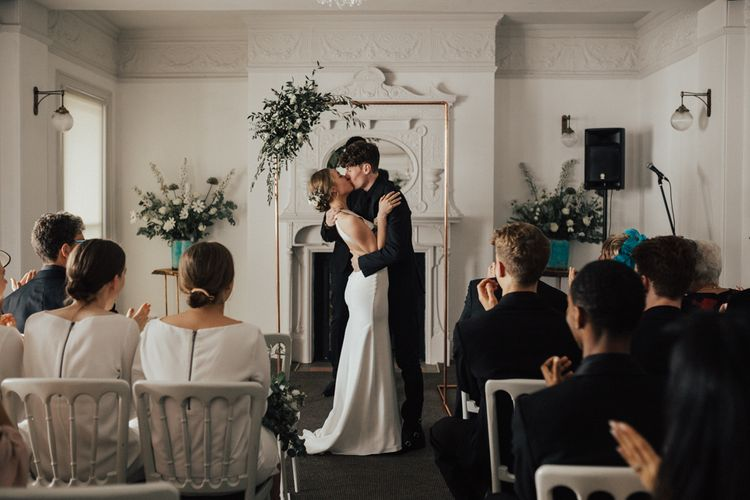 Bride In Sarah Seven Dress & Groom In All Black With Bridesmaids In White Shift Dresses And Foliage Decor With Images By Nataly J Photography