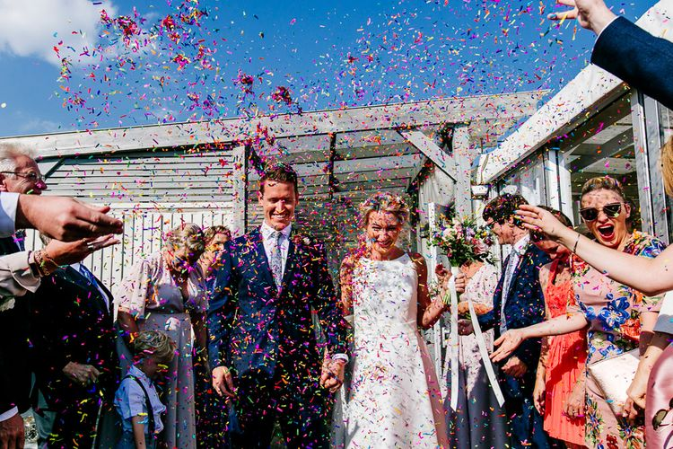 Confetti Exit   Bride in Jesus Peiro Wedding Dress   Groom in Navy Ted Baker Suit   Colourful Coastal Wedding at The Gallivant in Camber Sands with DIY Decor   Epic Love Story Photography