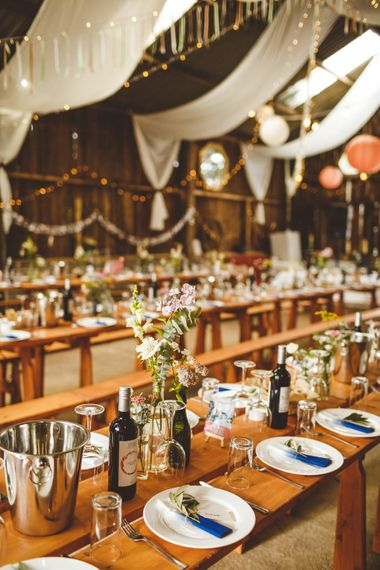 Wooden Trestle Tables With Bud Vases And White Drapes // Daisy By Halfpenny London For A Boho Barn Wedding In Yorkshire With Decor By Wild At Heart Weddings Images By Photography 34