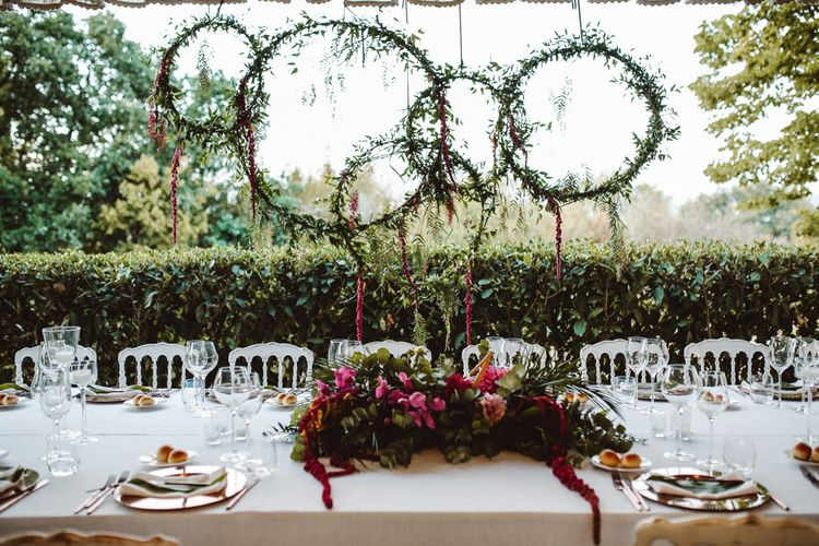 Greenery Hoops Top Table Backdrop | Tropical Green & Fuchsia Pink Outdoor Wedding at Castellina de Miremont, Italy Planned & Styled by Come le Ciliegie Wedding & Events | Images by Effeanfotografie | Film by Headshot Weddings