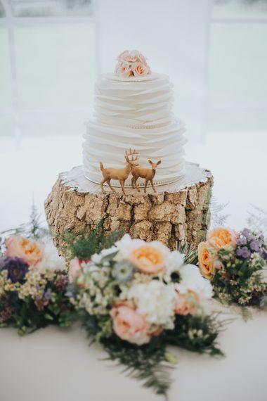 White Buttercream Wedding Cake On Log Slice