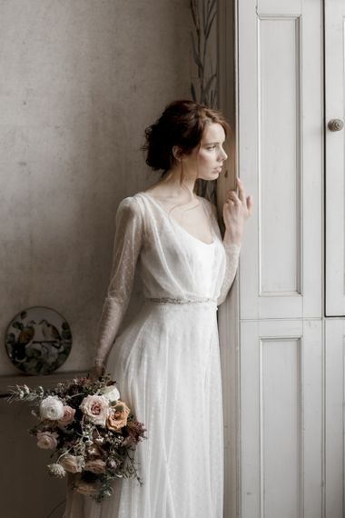 Beautiful Bride Standing at The Window Looking Outside