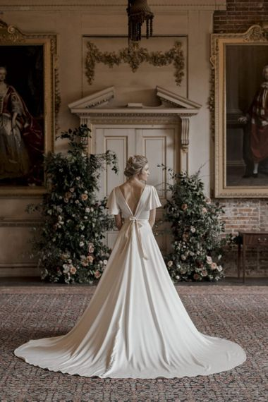 Bride in Satin Wedding Dress with Low Back and Ribbon Waist Detail