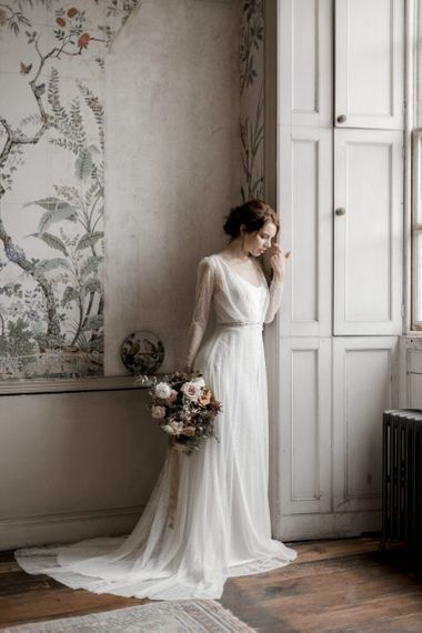 Bride in Lace Overlay Wedding Dress with Jewel Belt Standing at the Window of St Giles House