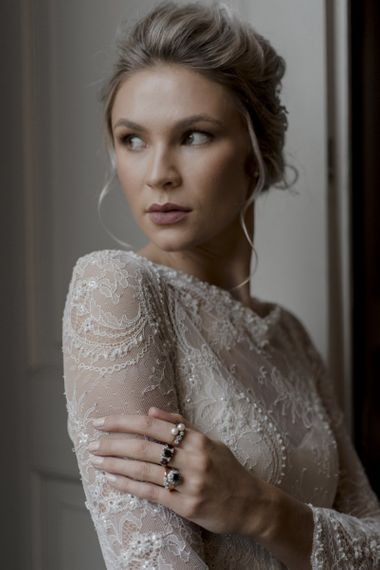 Bride in Delicate Lace Wedding Dress with Long Sleeves Wearing Stacking Rings