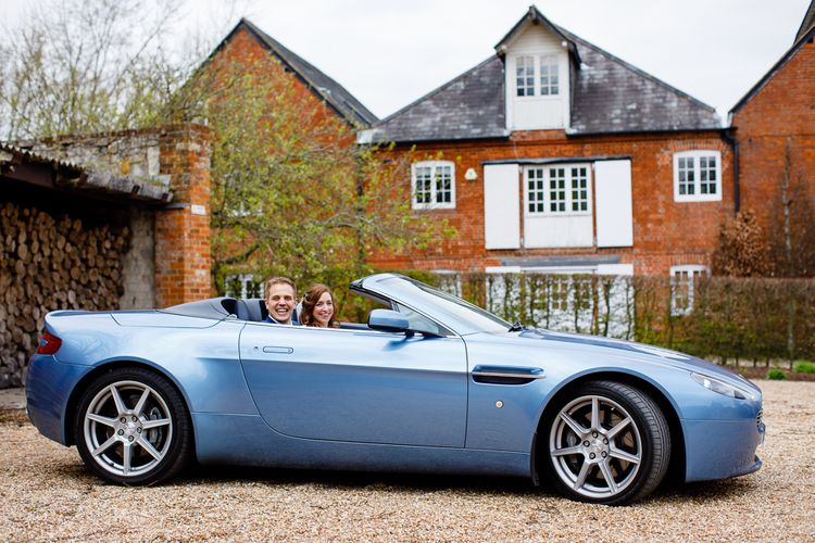 Bride and Groom Waving Everyone Off in their Something Blue Convertible Wedding Car