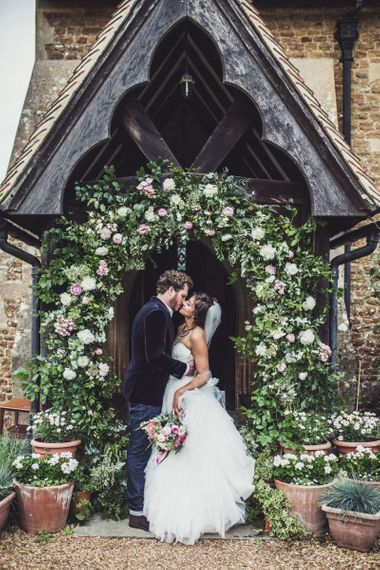 Bride and Groom Standing in Front of The Church Under a Floral Archway