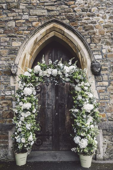 Floral Arch outside Church Entrance with Greenery and White Flowers including Hydrangeas