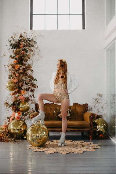 70s disco inspiration with gold glitter ball and roller skates decor