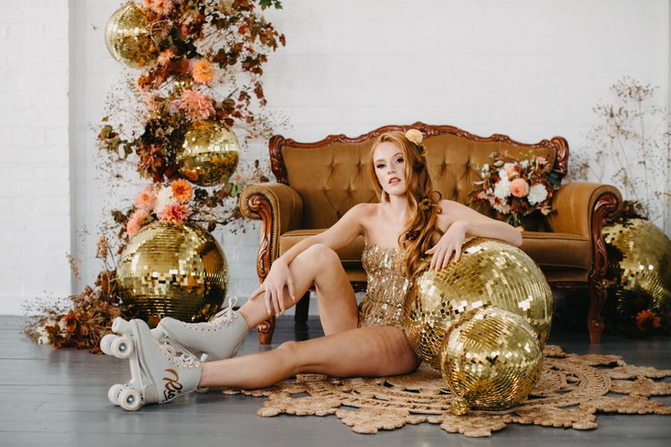 70s disco inspiration with gold glitter balls and rust coloured flowers