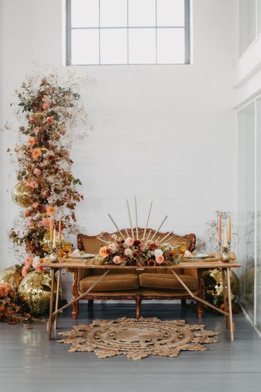 Tablescape with brown sofa and autumnal flower arrangement