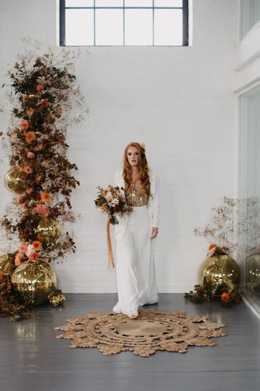 Bride in trouser suit with gold corset at 70s Disco wedding inspiration