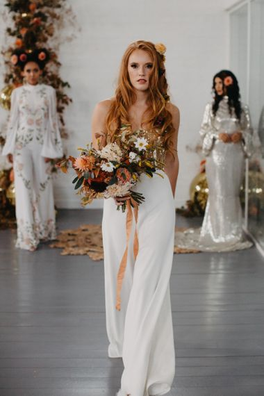 Bride in white trousers and gold corset holding an autumn bouquet