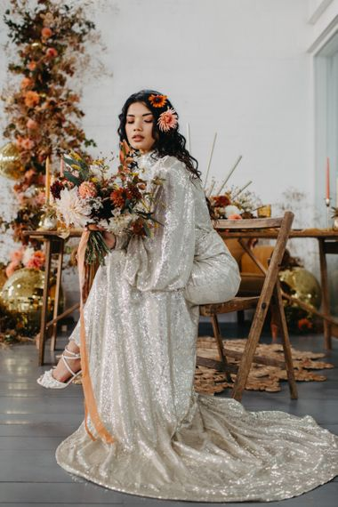 Bride in silver sequin wedding dress holding an autumnal bouquet for 70s Disco theme