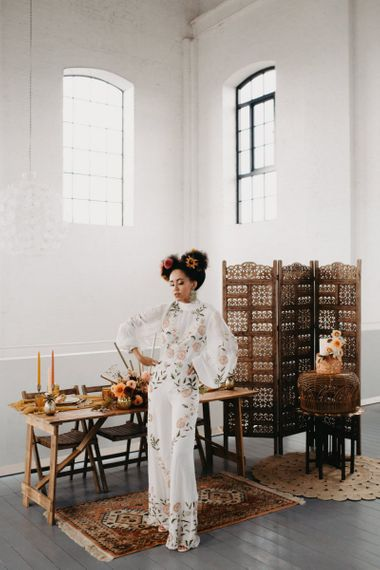 Bride in floral jumpsuit for 70s Disco themed wedding