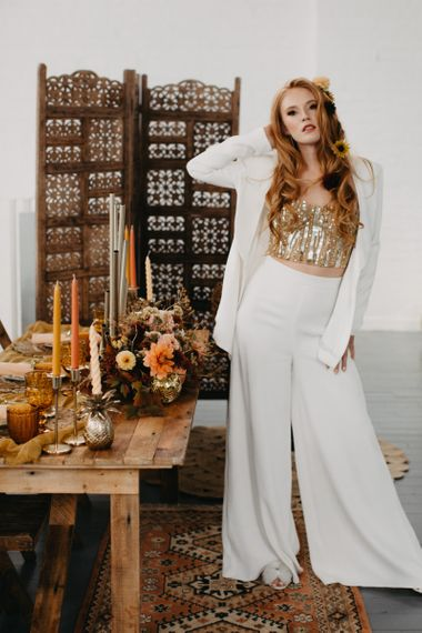 White trouser suit with gold corset for 70s Disco themed wedding