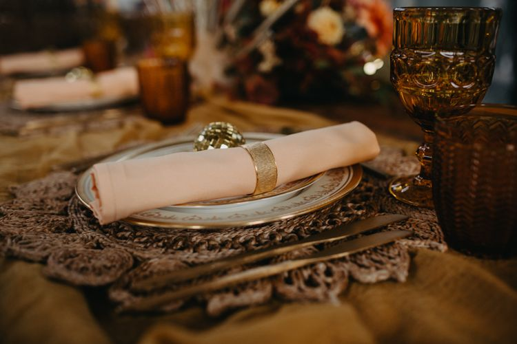 Place setting with brown mat, peach napkin and gold cutlery