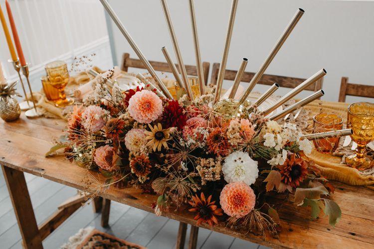 Floral centrepiece wedding decor with dahlias for 70s disco wedding theme