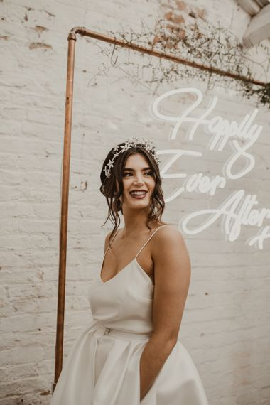 Hanging Neon Happily Ever After Sign on Cooper Frame Wedding Decor | Beautiful Bride in Spaghetti Strap Dress & Star Headdress |  Romantic Pink and Gold Wedding Inspiration in a Modern Summer House at Garthmyl Hall by KnockKnockPenny Studio | Nesta Lloyd Photography