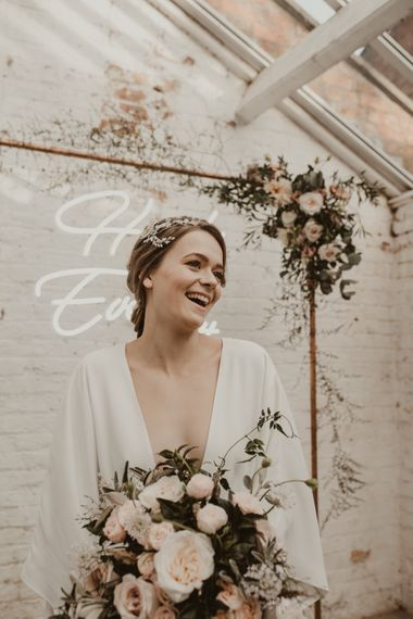 Hanging Neon Happily Ever After Sign on Cooper Frame Wedding Decor | Beautiful Bride in Wrap Wedding Dress & Vine Headpiece | Romantic Pink and Gold Wedding Inspiration in a Modern Summer House at Garthmyl Hall by KnockKnockPenny Studio | Nesta Lloyd Photography