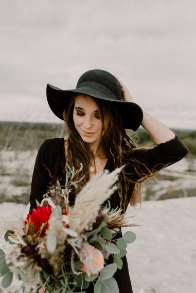 Bride in Portez Vos Idées Black Wedding Dress | Pampas Grass, Eucalyptus & Red Rose Wedding Bouquet | Wild Same Sex Couple Wedding Inspiration Shoot | Anne Letournel Photography